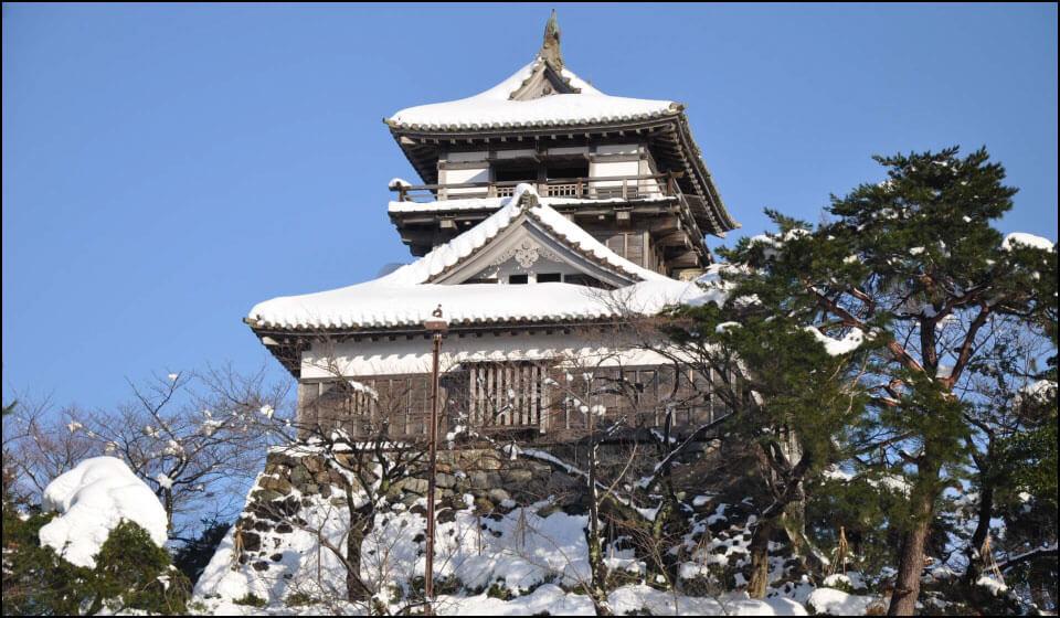 雪に覆われた丸岡城天守